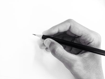 cropped-hand-of-person-holding-pencil-by-white-wall-681952377-59f0f299d088c00010f85526